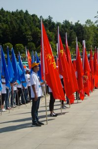 The flag-bearers are aligned in front of the scene