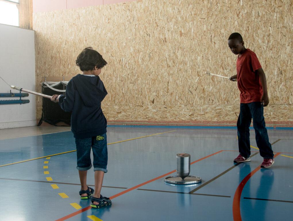 Des enfants  du centre de loisirs de Bourbriac s'exercent avec une toupie de 4 kg sur plateau.